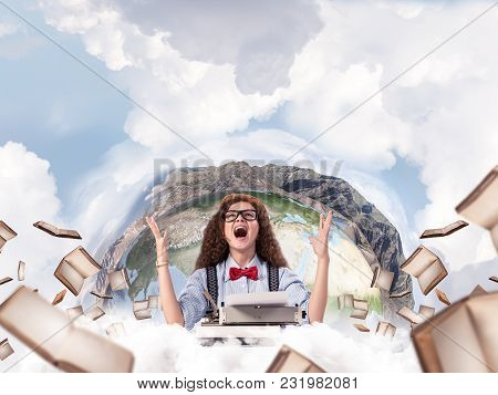 Happy And Young Woman Writer In Hat And Eyeglasses Looking Happy While Sitting With Typing Machine A