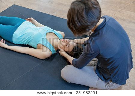 Crop Trainer Holding Head Of Peaceful Woman Doing Body-oriented Psychotherapy Lying On Mat.