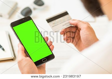 Online Payments Plastic Card A Black Smartphone With Green Screen For Chroma Key Compositing Hand Ho