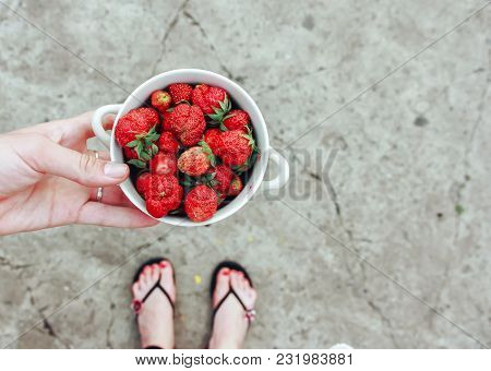 Woman Holds In Hand Wooden Bowl Of Fresh Strawberries On Concrete Gray Background