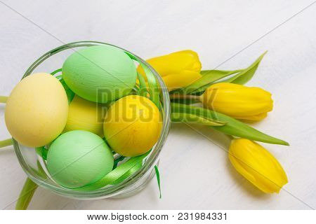 Happy Easter Greeting Background With Green And Yellow Painted Eggs In The Nest And Pink Tulips Near