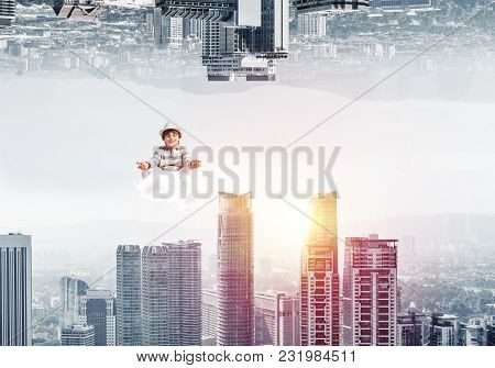 Young Boy Keeping Eyes Closed And Looking Concentrated While Meditating On Cloud In The Air Between