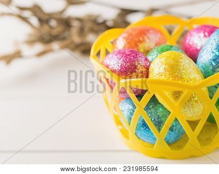 Basket With Colorful Eggs On A White Rustic Table. Decorations For The Easter Table.