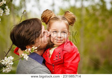 Family Time. The Father Holds A Small Daughter In A Leather Jacket. He Kisses Her On The Cheek. Spri