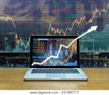 Stock Exchange Market Trading Graph Over The Screen Of Computer Laptop On Wood Table Over The Photo