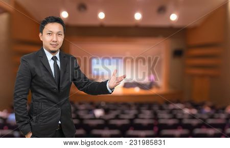 Businessman With Welcoming Gesture On Abstract Blurred Photo Of Conference Hall Or Seminar Room With
