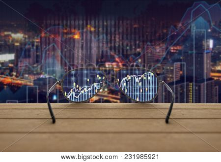 Stock Exchange Market Trading Graph Focused In Glasses Lenses On The Wooden Over The Abstract Photo