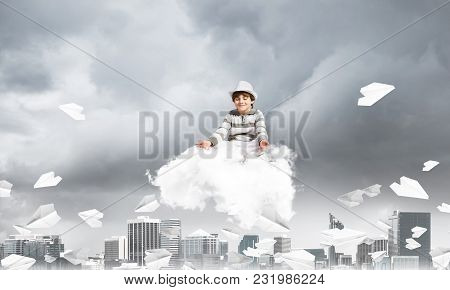 Young Little Boy Keeping Eyes Closed And Looking Concentrated While Meditating On Cloud Among Flying