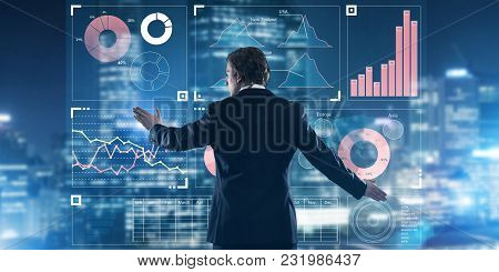 Back View Of Businessman Working With Virtual Panel And Night City At Background