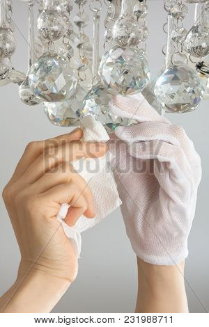 Hands Of Woman Cleaning The Chandelier With Rag, Closeup