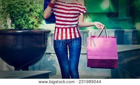 Part Of Woman With Shopping Bags Walking On Street