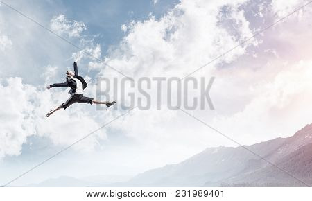Attractive Business Woman In Suit Jumping In The Air As Symbol Of Active Life Position. Skyscape Wit