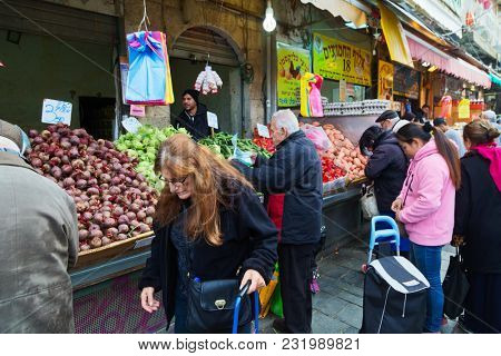 JERUSALEM, ISRAEL - DECEMBER 29, 2016: Shoppers at front of Mahane Yehuda market in Jerusalem.  More than 250 traders on market sell fresh fruits and vegetables, baked products, fish, meat and others