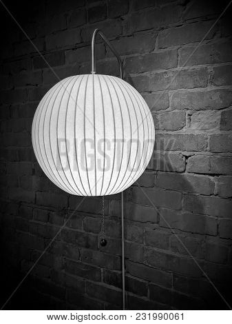 Lamp With Round Lampshade On Brick Wall. Image In Black And White Tones, With Vignette.