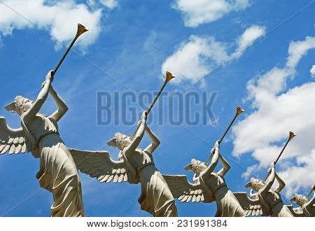 Angels With Trumpets Aiming Towards Heaven With The Sky In The Background.