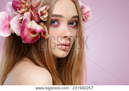 Beautiful girl, isolated on a light - violet  background with varicoloured flowers in hairs, emotions, cosmetics