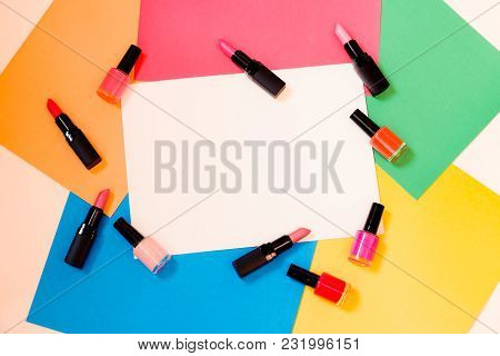 Lipstics And Nail Polishes On Colorful Paper Background