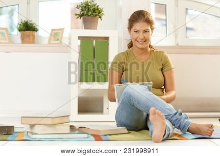 Happy young woman sitting on floor at home, learning, writing into exercise book, smiling.
