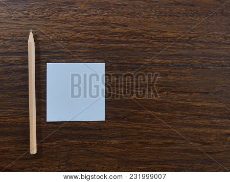 White Square Blank Paper And Natural Brown Wood Pencil Putting On Dark Brown Wood Table With Copy Sp