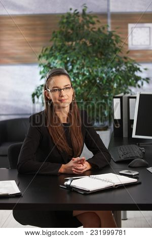 Portrait of young confident businesswomen at her office desk.