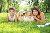 Mother and her two sons in the park with a golden retriever dog poster