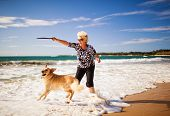Happy woman playing on the beach with golden retriever poster