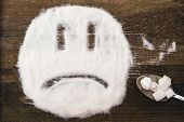Face of a sad smiley made with granulated sugar. The picture illustrates the harm of eating sugar and salt, as well as dependence on flavoring additives. poster