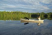 Canoeist with Black Labrador Retriever in the Bow poster