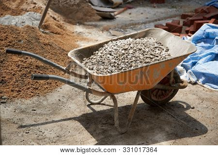 wheel barrow of building material sand  rock and cement for construction