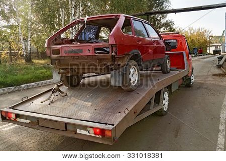 A Tow Truck Towing A Wrecked Car To A Junkyard Of Old Cars. Evacuator With A Car Body.