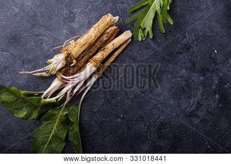 Fresh Orgaanic Horseradish Or Horse-radish Root On Wooden Cutting Board.  Top View