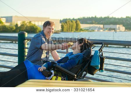 Caucasian Father In Early Fifties Feeding Disabled Thirteen Year Old Son In Wheelchair A Hamburger O