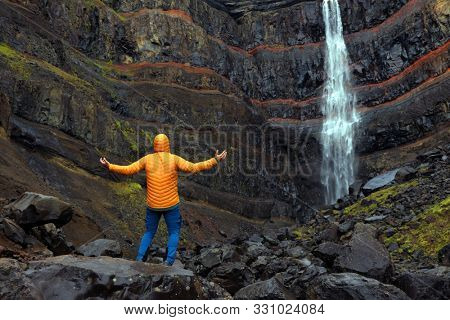 Tourist in front of Hengifoss waterfall,  the third highest waterfall in Iceland, surrounded by basaltic strata with red layers of clay between the basaltic layers.