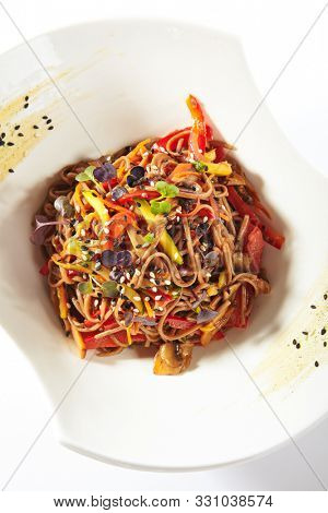 Top view of japanese soba, yakisoba or nagano soba with vegetables in sweet and sour sauce. Thin buckwheat noodles, pasta or tagliatelle with greens and sesame on white restaurant plate isolated