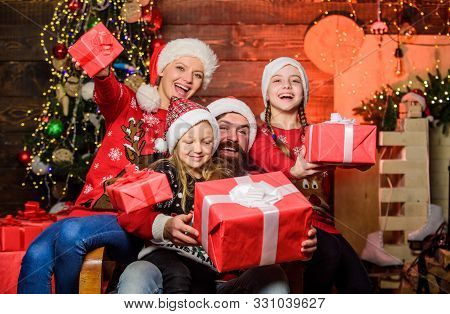 Christmas Joy. Happy Holidays. Parents And Children Opening Christmas Gifts. Father Santa Claus And