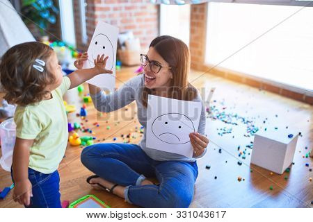 Young beautiful psicologist and toddler doing therapy using emoji emotions at kindergarten
