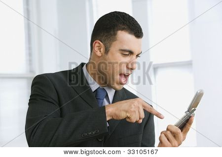 Hispanic businessman yelling at cell phone