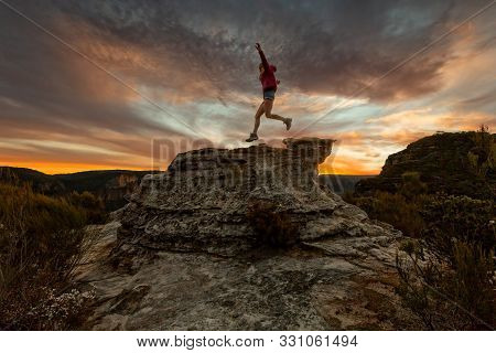 Active Fit Woman Leaping Across Rocks Of Mountain Cliffs At Sunset.  Be The Best Person You Can.  Co
