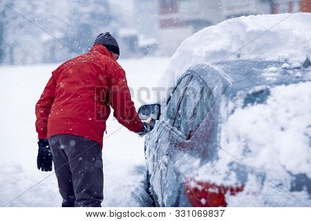 Snow Covered Car. Man Brushing The Snow Off His Car On A Cold Winter Day
