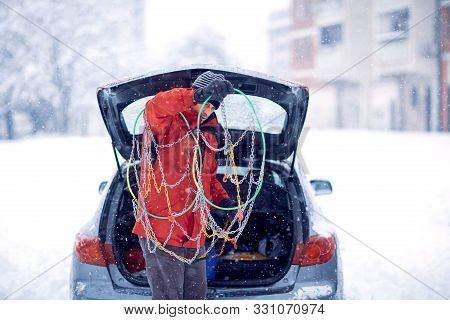 Confused Man Does Not Know How To Put Snow Chains On Car Tire.confused Man With Gloves Install Snow