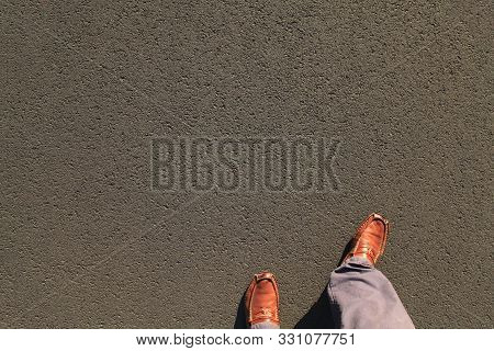 Feet In Shoes (loafers Or Moccasins) On Asphalt Surface. Detailed Texture Background Of The Bitumen
