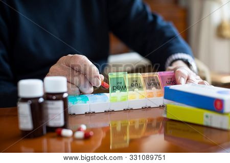 Close Up Of Senior Man Organizing Medication Into Pill Dispenser