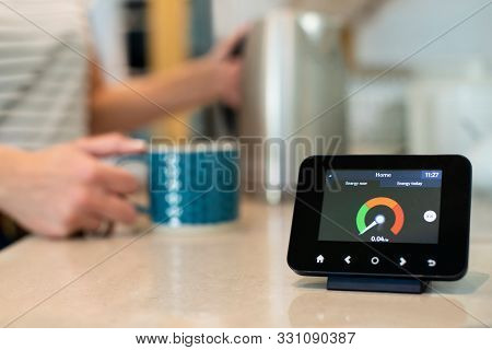 Woman At Home Boiling Kettle For Hot Drink With Smart Energy Meter In Foreground