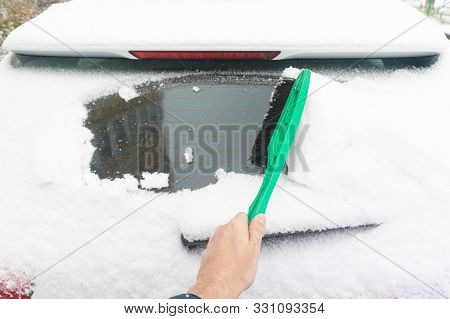 Man Cleaning Car From Snow With Brush. Snow-covered Car Windshield. Parked Car Covered With Snow Dur