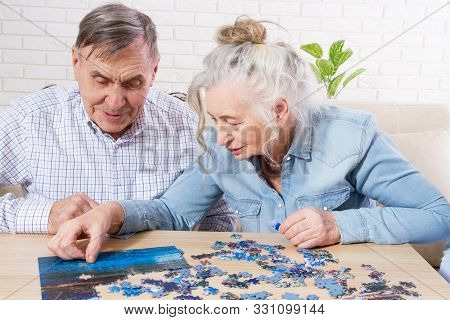 Senior Couple Solving Jigsaw Puzzle Together At Home