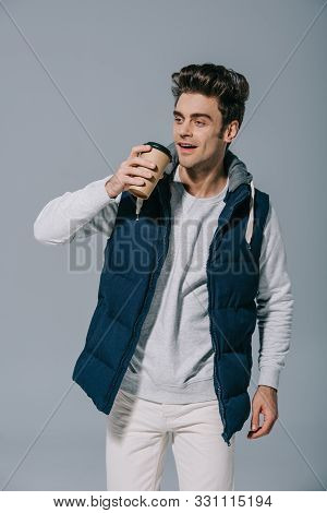Happy Handsome Man In Warm Waistcoat Drinking Coffee To Go, Isolated On Grey