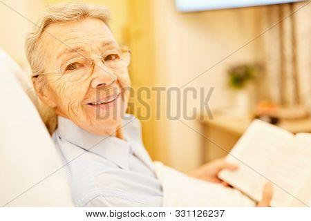 Happy senior retired woman is reading a book in her senior citizen home