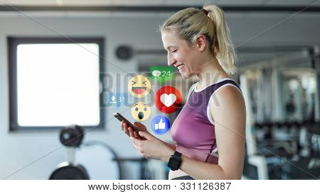 Young woman as social media influencer using smartphone in fitness center