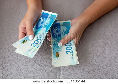 Close Up Of A Girl Counting Israeli Money. Counting 200 Israeli Shekel Bills Close Up On Large Amoun