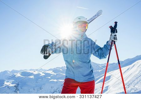 Photo of sportsman in helmet and mask with skis on his shoulder at winter resort